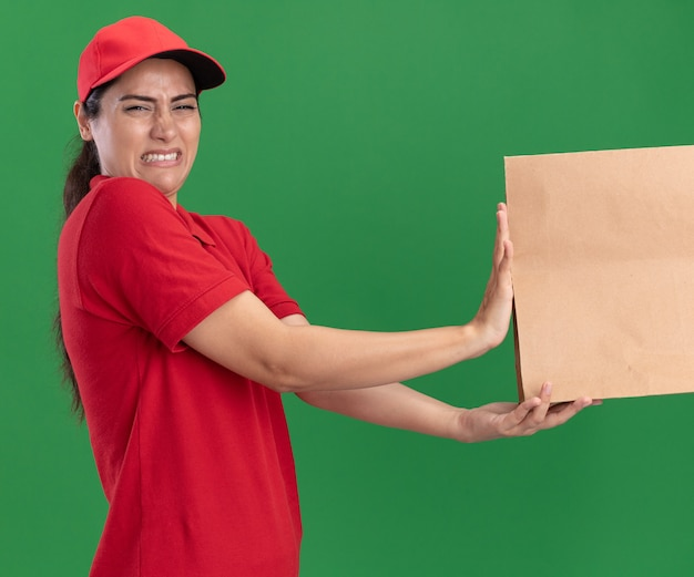 Squeamish jeune livreuse portant l'uniforme et une casquette donnant un paquet de nourriture en papier au client isolé sur mur vert