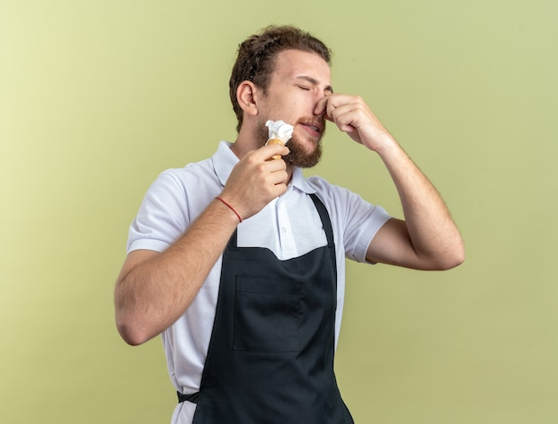 Squeamish avec les yeux fermés jeune homme barbier portant uniforme appliqué de la crème à raser avec un blaireau saisi le nez isolé sur fond vert olive