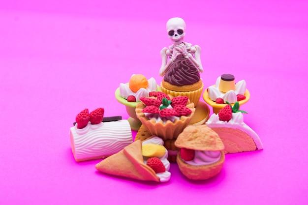 Squelette assis sur la boulangerie, profitez de manger jusqu'à la mort avec des desserts sucrés.