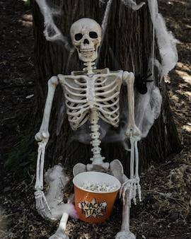 Squelette assis près d'un arbre avec du pop-corn