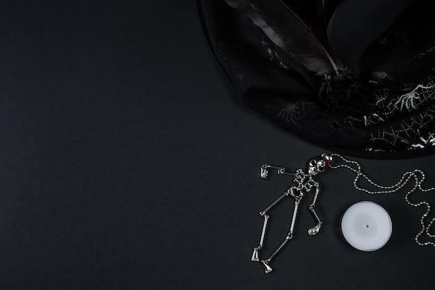 Squelette, chapeau de sorcière et bougie. symboles d'halloween sur fond noir.