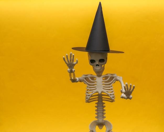 Squelette dans un chapeau de sorcière sur fond jaune. thème effrayant et halloween