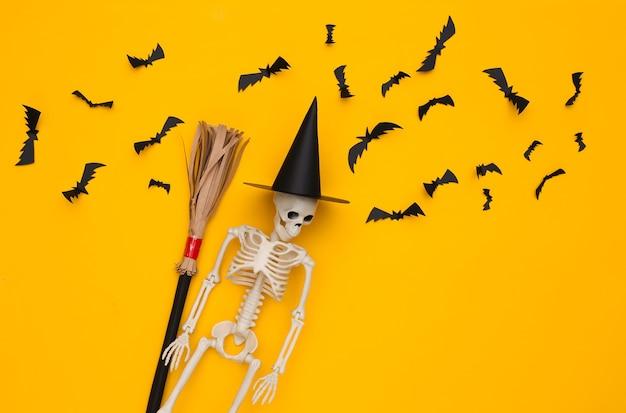 Squelette dans un chapeau de sorcière et un manche à balai, chauves-souris volantes sur fond jaune. décor fait main d'halloween. vue de dessus. mise à plat