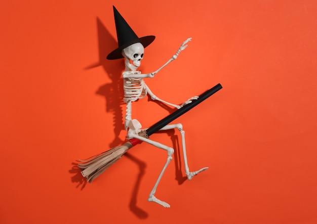 Squelette dans un chapeau de sorcière sur un manche à balai. fond clair orange. concept minimaliste d'halloween. vue de dessus. mise à plat