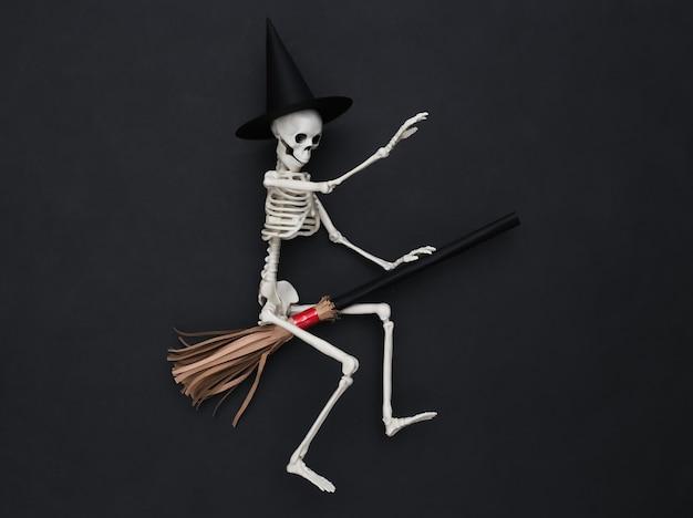 Squelette dans un chapeau de sorcière sur un manche à balai. fond noir. concept minimaliste d'halloween. vue de dessus. mise à plat
