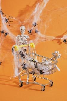 Squelette de décor en plastique et caddie sur fond marron, shopping sur concept halloween, toiles d'araignées et araignées sur fond