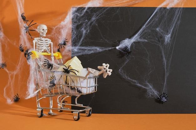 Squelette de décor en plastique et caddie sur fond marron, shopping sur concept hallown, toiles d'araignées et araignées sur l'arrière-plan, espace de copie de plaque noire