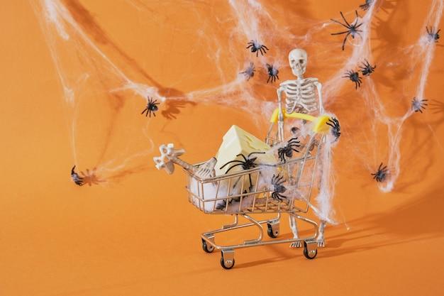 Squelette de décor en plastique et caddie sur fond marron, shopping pour le concept d'halloween
