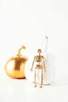 Squelette doré d'halloween à côté de citrouilles décoratives blanches et dorées sur fond clair