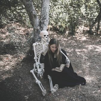 Squelette femme embrassant avec livre dans des vêtements de sorcière