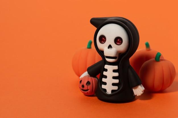Squelette d'halloween dans un manteau noir avec des citrouilles sur fond orange. fond de jouets halloween avec espace de copie.