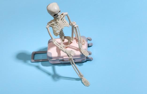 Squelette de jouet avec valise de voyage sur bleu. concept de voyage