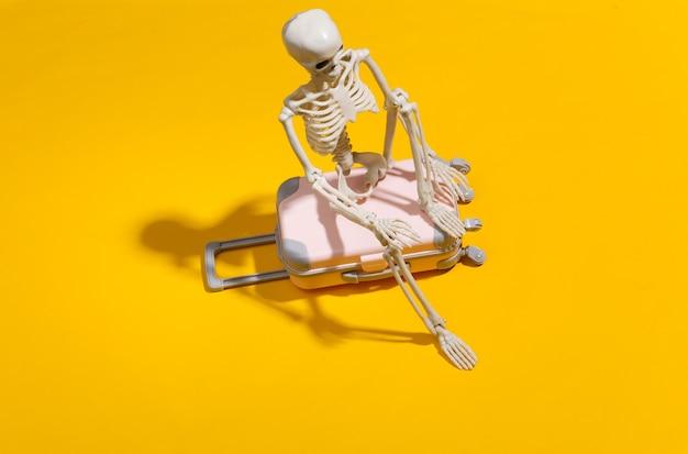 Squelette de jouet avec valise de voyage sur jaune vif. concept de voyage