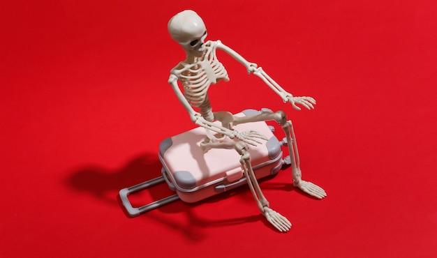 Squelette de jouet avec valise de voyage sur un rouge. concept de voyage