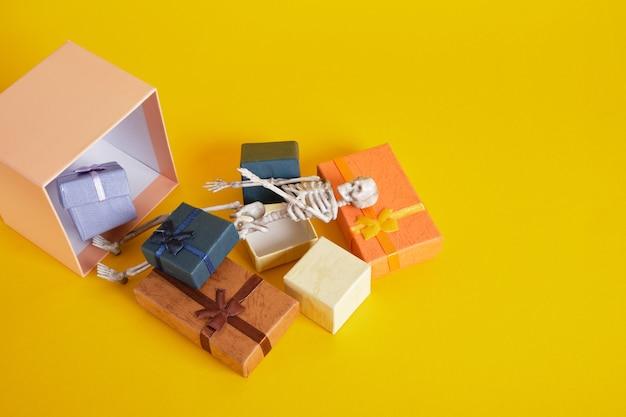 Squelette en plastique et coffrets cadeaux sur jaune
