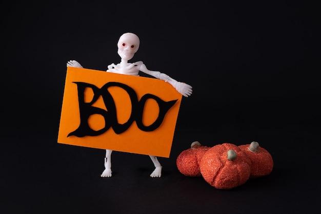 Squelette tenant une affiche avec les mots boo et citrouilles de guimauve sur fond noir, concept d'halloween, gros plan.