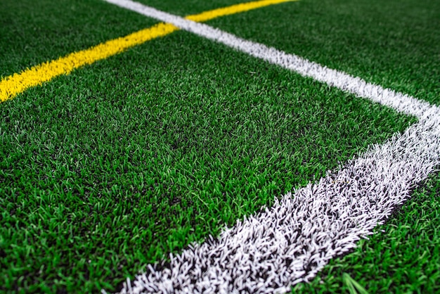 Stade de terrain de football universitaire ou scolaire, fond d'herbe verte.