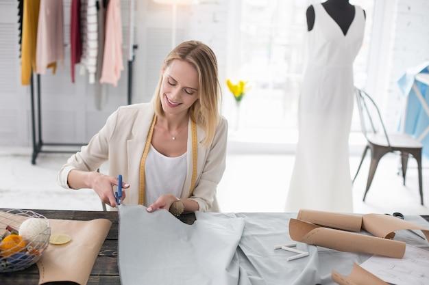 Stage dans la mode. couturière habile travaillant avec du tissu et utilisant des ciseaux
