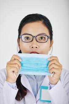 Stagiaire couvrant le visage avec un masque médical