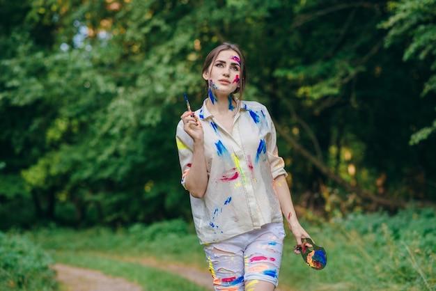 Stained femme peinture marche à travers un champ avec des arbres