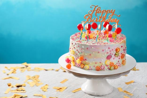Stand avec beau gâteau d'anniversaire savoureux sur la table contre la couleur