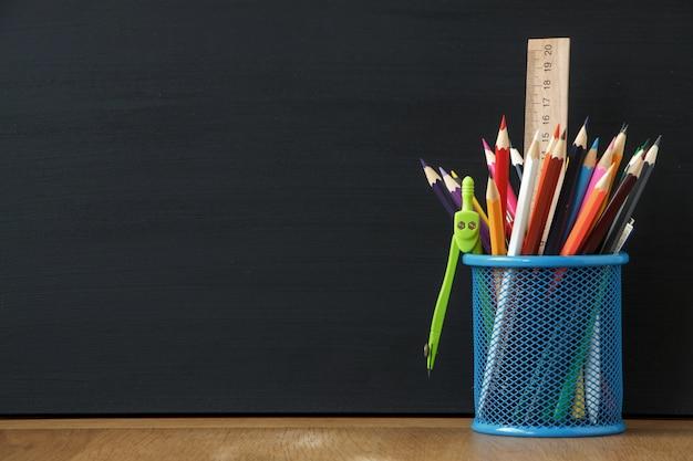 Stand bleu gros plan avec des fournitures scolaires sur le fond d'un grand tableau de craie noire