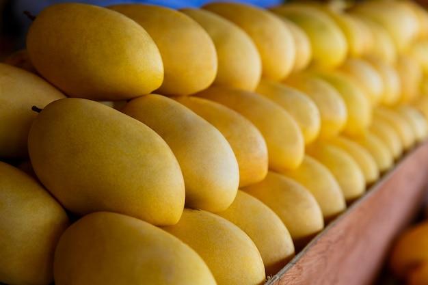 Stand du festival de la mangue avec des fruits de mangue jaune frais dans la mise au point sélective du marché de rue