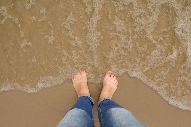 Stand féminin sur la plage de sable d'été