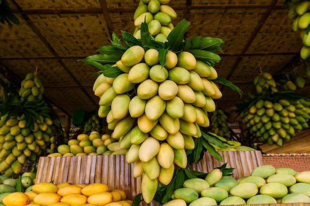 Stand de festival de mangue avec des fruits de mangue jaune frais sur le marché de rue