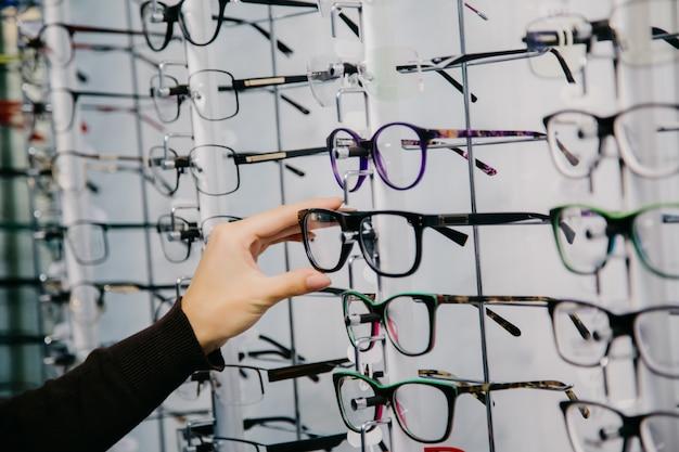 Stand avec des lunettes dans le magasin d'optique