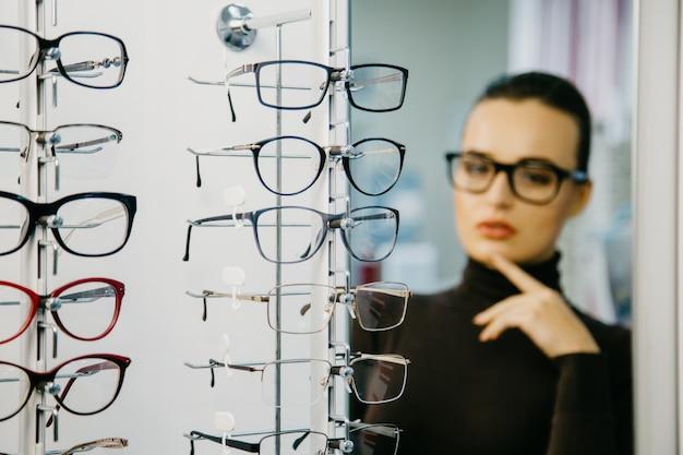 Stand avec des lunettes dans le magasin d'optique.