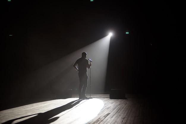 Stand up comédien sur scène dans le faisceau de lumière.