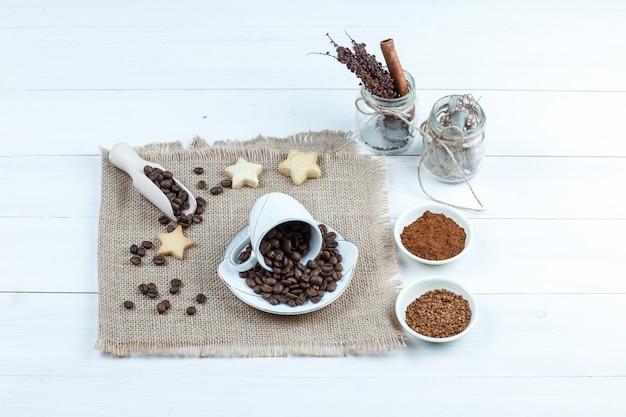 Star cookies, grains de café sur un morceau de sac avec bol de café instantané, pot d'herbes gros plan sur un fond de planche de bois blanc