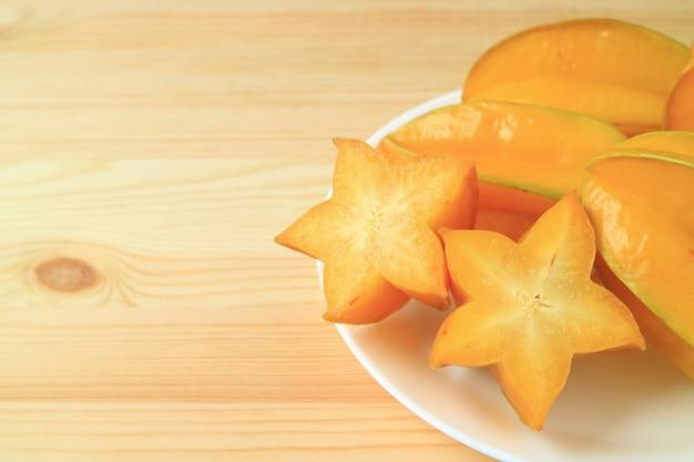 Star fruit aux couleurs vives, tranché et entier sur une table en bois, avec espace libre pour le texte et le design