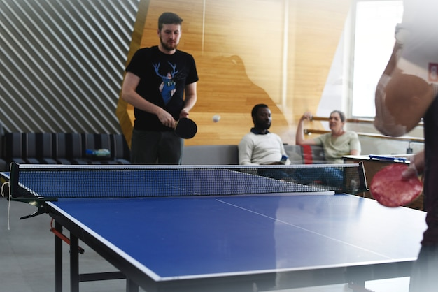 Startup business people jouant au tennis de table ensemble pendant la pause