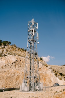 Station de base cellulaire près de l'autoroute contre la surface des montagnes