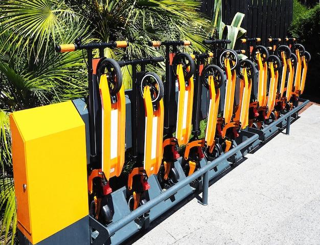 Station de location de scooters kick dans un parc public. matériel de transport plié