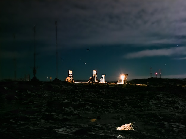 Station météorologique polaire sous la lumière de la pleine lune sur une colline au bord de la mer de barents