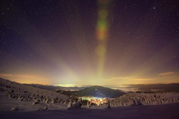 La station de ski éclairée la nuit est située dans un endroit pittoresque au-dessus d'un ciel étoilé clair. concept de vacances à la campagne.