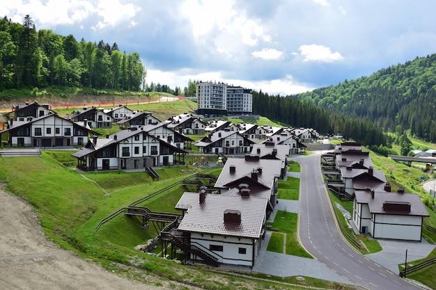 Une station de ski en été avec des rangées d'hôtels bas du même type aux toits bruns sur fond de ciel bleu vif et de montagnes couvertes de forêts