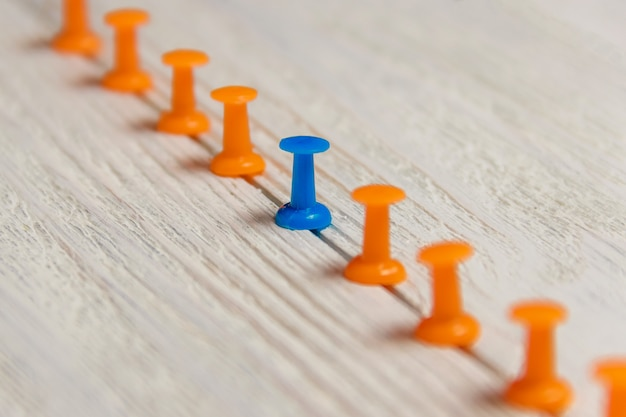 Stationnaire, punaise bleue en ligne avec orange, concept de différence, individualité, leadership. niveau inférieur. copiez l'espace.