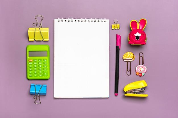 Stationnaire, retour à l'école, heure d'été, créativité et concept d'éducation fournitures scolaires - loupe, crayons, stylo, trombones, agrafeuse et bloc-notes sur fond violet, pose à plat mock up vue de dessus.