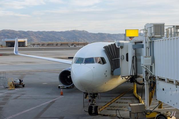 Le stationnement à l'avion de passagers à la porte du terminal à la passerelle d'embarquement connectée est chargé de bagages