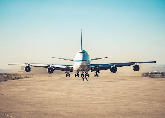 Stationnement d'avion sur une piste d'aéroport en journée ensoleillée.