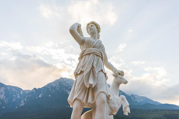 La statue d'artémis et un cerf près de la ville de brasov en roumanie