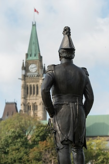 Statue avec le bâtiment du parlement en arrière-plan, colline du parlement, ottawa, ontario, canada