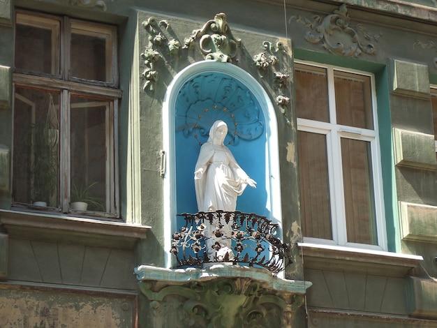 Statue blanche d'une fille sur un balcon sur la façade d'un immeuble ancien