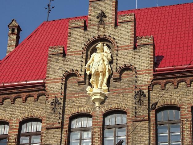 Statue Blanche D'un Homme Sur La Façade D'un Immeuble En Brique Au Toit Rouge Photo Premium