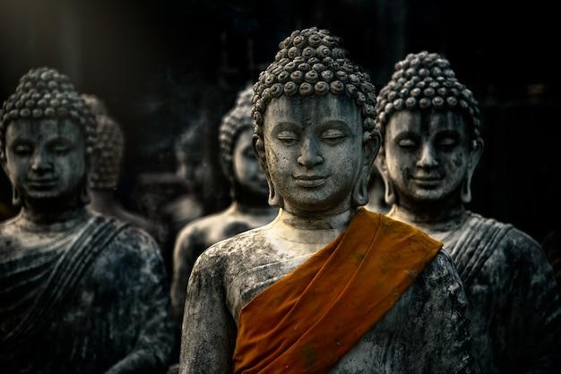 Statue de bouddah avec anciens stupas dans un temple bouddhiste à saraburi, thaïlande
