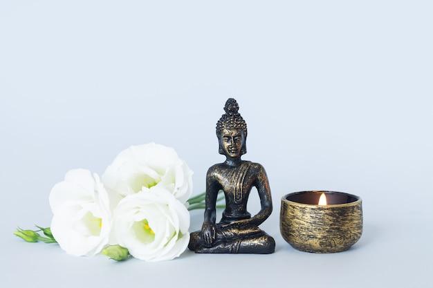 Statue de bouddha sur l'autel avec bougie et fleurs. concept de méditation, de bouddhisme et d'illumination